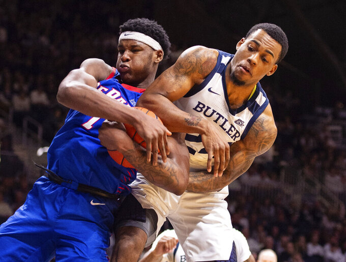 DePaul forward Romeo Weems, left, and Butler forward Markeese Hastings, right, battle for a rebound during the second half of an NCAA college basketball game, Saturday, Feb. 29, 2020, in Indianapolis. (AP Photo/Doug McSchooler)