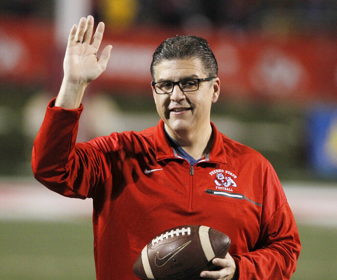 FILE - In this Nov. 4, 2017 file photo, Fresno State president Joseph I. Castro waves to the crowd before an NCAA college football game against BYU in Fresno, Calif. Castro was chosen to be the new chancellor of the California State University, becoming the first Mexican-American and native Californian to lead the nation's largest four-year public university system. The CSU Board of Trustees announced the appointment of Castro on Wednesday, Sept. 23, 2020. He will replace Chancellor Timothy White, who is retiring. (AP Photo/Gary Kazanjian, File)