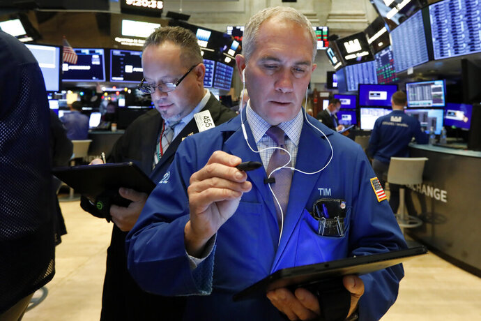 Traders Robert Arciero, left, and Timothy Nick work on the floor of the New York Stock Exchange, Wednesday, Dec. 4, 2019. Stocks are opening broadly higher as traders became more hopeful that a trade deal between the U.S. and China was making progress. (AP Photo/Richard Drew)