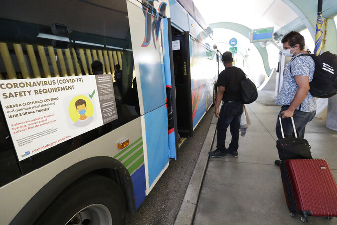 Passengers practice social distancing as they board a bus at Dadeland South Station, Friday, April 24, 2020, in Miami. Miami-Dade County continues to be Florida's coronavirus epicenter with a third of the state's confirmed cases. (AP Photo/Wilfredo Lee)