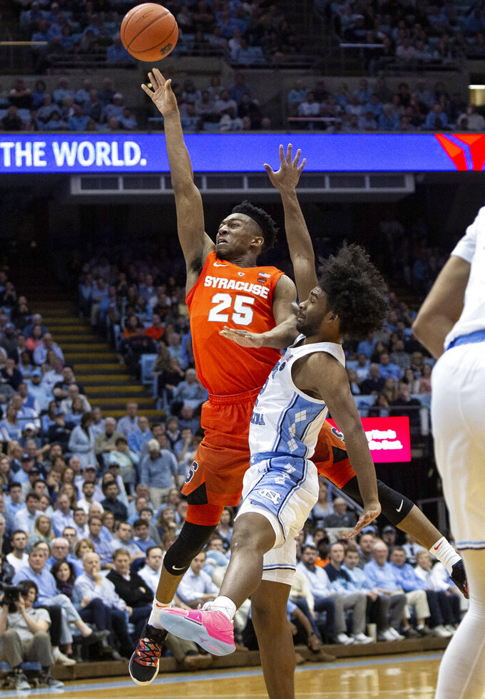 CORRECTS TO COBY WHITE AND NOT COLBY AS ORIGINALLY SENT - Syracuse's Tyus Battle (25) attempts a shot next to North Carolina's Coby White, right, during the second half of an NCAA college basketball game in Chapel Hill, N.C., Tuesday, Feb. 26, 2019. (AP Photo/Ben McKeown)