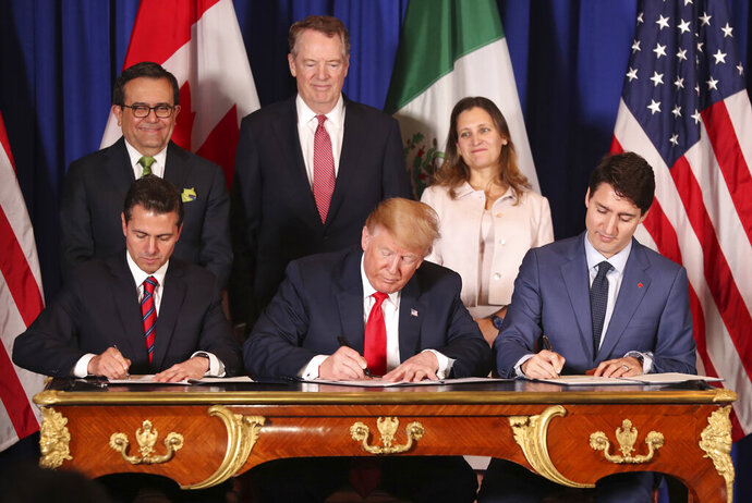 FILE - In this Nov. 30, 2018 file photo, President Donald Trump, center, sits between Canada's Prime Minister Justin Trudeau, right, and Mexico's President Enrique Pena Nieto as they sign a new United States-Mexico-Canada Agreement that is replacing the NAFTA trade deal, during a ceremony at a hotel before the start of the G20 summit in Buenos Aires, Argentina. Trump's new North America trade agreement would give the U.S. economy only a modest boost, an independent federal agency finds. (AP Photo/Martin Mejia, File)