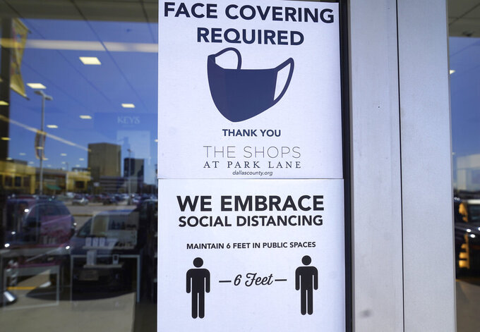 Signs tells customers about safety measures against COVID-19 that are required inside a retail store Tuesday, March 2, 2021, in Dallas. Texas is lifting a COVID-19 mask mandate that was imposed last summer but has only been lightly enforced. Republican Gov. Greg Abbott's announcement Tuesday makes Texas the largest state to do away with a face covering order. (AP Photo/LM Otero)