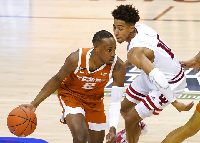 Texas guard Matt Coleman III (2) drives around Indiana guard Rob Phinisee (10) in the first half of a semifinal NCAA college basketball game in the Maui Invitational tournament, Tuesday, Dec. 1, 2020, in Asheville, N.C. (AP Photo/Kathy Kmonicek)