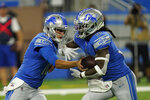 Detroit Lions quarterback Jared Goff, left, hands off to running back Jamaal Williams (30) during the first half of a preseason NFL football game against the Buffalo Bills, Friday, Aug. 13, 2021, in Detroit. (AP Photo/Paul Sancya)