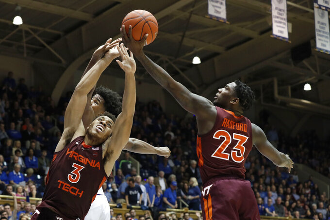Virginia Tech guard Wabissa Bede (3) and guard Tyrece Radford (23) reach for a rebound with Duke center Vernon Carey Jr. during the second half of an NCAA college basketball game in Durham, N.C., Saturday, Feb. 22, 2020. (AP Photo/Gerry Broome)