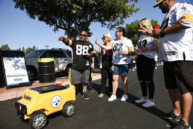 Fans stand in front of a remote controlled cooler prior to an NFL football game between the Pittsburgh Steelers and the Los Angeles Chargers, Sunday, Oct. 13, 2019, in Carson, Calif. (AP Photo/Kelvin Kuo)