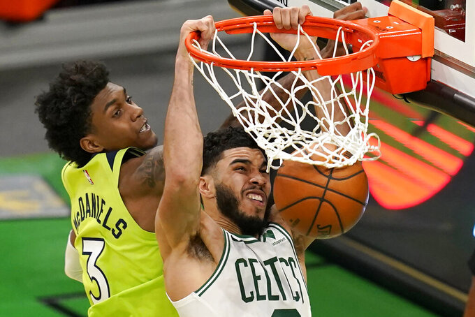 Boston Celtics forward Jayson Tatum, right, dunks against Minnesota Timberwolves forward Jaden McDaniels (3) in the third quarter of an NBA basketball game, Friday, April 9, 2021, in Boston. (AP Photo/Elise Amendola)