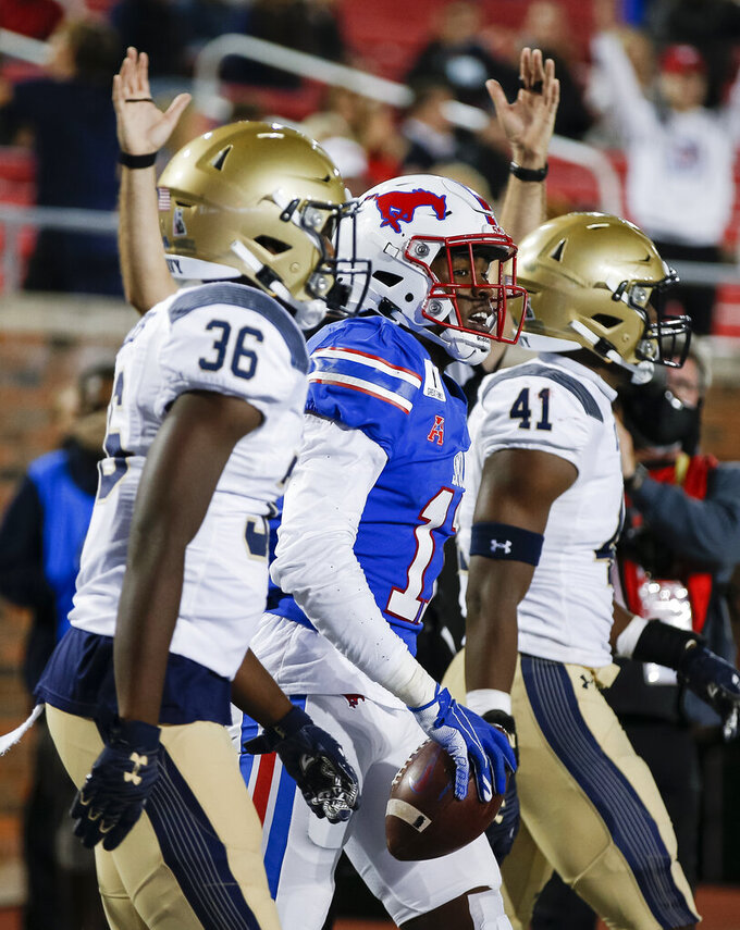 Navy safety Derek Atwaters (36) and linebacker Terrell Adams (41) walk past SMU wide receiver Rashee Rice, center, who scored a touchdown during the second half of an NCAA college football game Saturday, Oct. 31, 2020, in Dallas. (AP Photo/Brandon Wade)