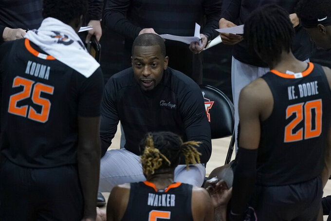 Oklahoma State head coach Mike Boynton talks to his team during the second half of an NCAA college basketball game against Baylor in the semifinals of the Big 12 tournament in Kansas City, Mo., Friday, March 12, 2021. (AP Photo/Charlie Riedel)