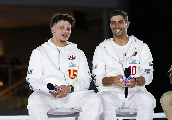 Kansas City Chiefs' Patrick Mahomes, right, chats with San Francisco 49ers' Jimmy Garoppolo during Opening Night for the NFL Super Bowl 54 football game Monday, Jan. 27, 2020, at Marlins Park in Miami. (AP Photo/David J. Phillip)