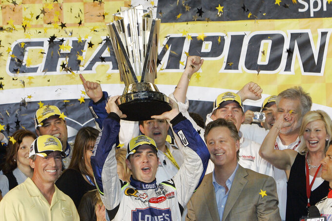 FILE - In this Nov. 18, 2007, file photo, Jimmie Johnson, center, celebrates after winning the NASCAR Nextel Cup Series championship in Homestead, Fla. NASCAR CEO Brian France is at right, and Nextel chief marketing officer Tim Kelly is on left. Jimmie Johnson is the latest NASCAR superstar to climb out of his car, with the seven-time champion announcing Wednesday, Nov. 20, 2019, that 2020 will be his final season of full-time racing. (AP Photo/Alan Diaz, File)