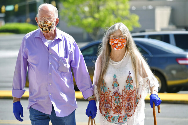 Bud and Elizabeth Neal wear masks to protect agains coronavirus, as they walk through the parking lot after the Anderson Mall opened to limited business on Friday, April 24, 202 in Anderson, S.C.   Gov. Henry McMaster eased restrictions on Friday.  (AP Photo/Richard Shiro)