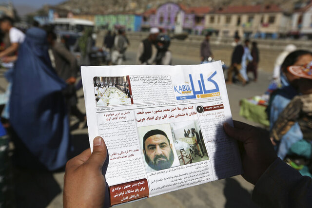 FILE - In this May 25, 2016, file photo, an Afghan man reads a local newspaper with photos the former leader of the Afghan Taliban, Mullah Akhtar Mansoor, who was killed in a U.S. drone strike last week, in Kabul, Afghanistan. A Pakistani judge ordered the auction of five properties purchased by former Taliban chief Mullah Akhtar Mansour with fake documents before he was killed in a U.S. drone strike in 2016, two investigators familiar with the case said Friday, May 8, 2020. (AP Photo/Rahmat Gul, File)