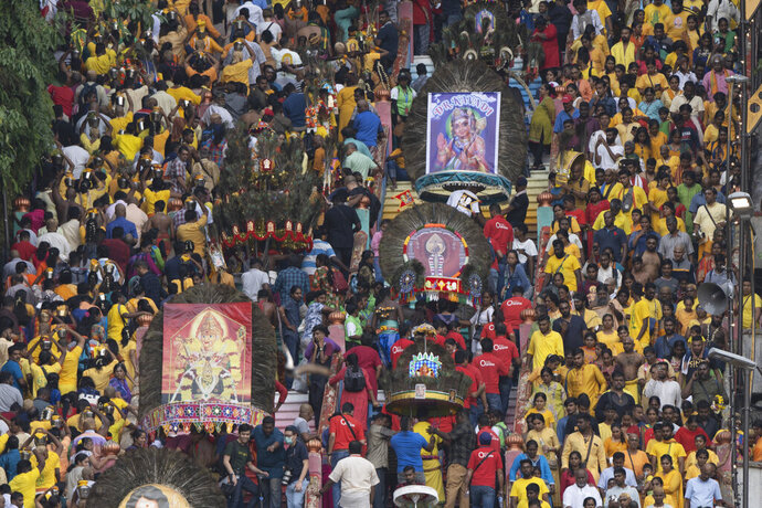 In this Feb. 8, 2020, photo, Hindu devotees carry giant Kavadi offering cages in a procession during the Thaipusam festival at Batu Caves, in Selangor, Malaysia. Tens of thousands of ethnic Hindus, meanwhile, gathered last weekend to celebrate the annual festival, undeterred by the outbreak of a new virus. (AP Photo/Vincent Thian)