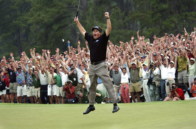 FILE - In this April 11, 2004, file photo, Phil Mickelson celebrates after winning the Masters golf tournament with a nine-under-par at the Augusta National Golf Club in Augusta, Ga. Augusta National decided Friday, March 13, 2020, to postpone the Masters because of the spread of the coronavirus. Club chairman Fred Ridley says he hopes postponing the event puts Augusta National in the best position to host the Masters and its other two events at some later date. Ridley did not say when it would be held. (AP Photo/Dave Martin, File)
