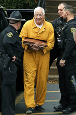 Former Penn State University assistant football coach Jerry Sandusky, center, arrives at the Centre County Courthouse, Friday, Nov. 22, 2019, in Bellefonte, Pa., to be resentenced after an appeals court said mandatory minimum sentences had been improperly applied against him.   (AP Photo/Gene J. Puskar)