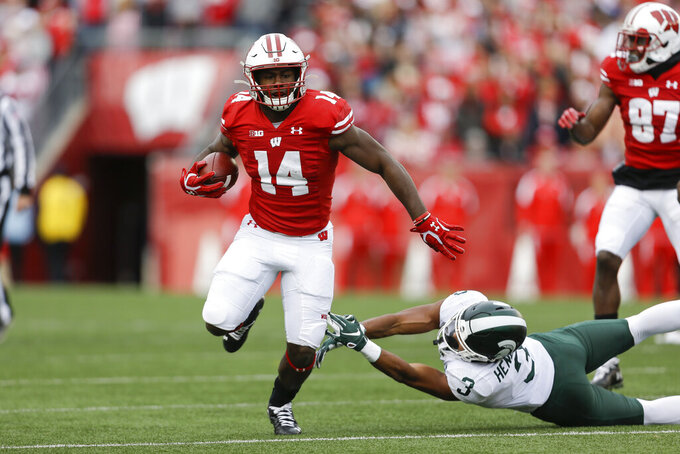 """FILE - In this Oct. 12, 2019, file photo, Wisconsin running back Nakia Watson (14) runs past Michigan State safety Xavier Henderson (3) during the first half of an NCAA college football game, in Madison, Wis. Even after beating a Wisconsin team that was favored by 30 ½ points last year, Illinois heads into Madison as a 19 ½-point underdog as the two West Division rivals prepare to open the pandemic-delayed Big Ten season Friday night.  """"Illinois definitely deserves a butt-whooping from last year,"""" Wisconsin running back Nakia Watson said earlier this month. (AP Photo/Andy Manis, File)"""