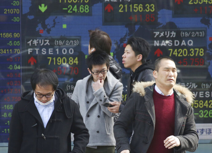 In this Thursday, Feb. 14, 2019, photo, people walk by an electronic stock board of a securities firm in Tokyo. Asian shares were broadly lower on Friday, Feb. 15, 2019, tracking a weak Wall Street session as traders awaited the conclusion of U.S.-China talks in Beijing. (AP Photo/Koji Sasahara)