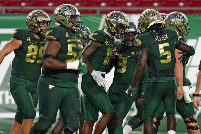 South Florida safety DeVontres Odoms-Dukes (18) celebrates his touchdown catch against Citadel with teammatesm including quarterback Jordan McCloud (3) and wide receiver Randall St. Felix (5) during the first half of an NCAA college football game Saturday, Sept. 12, 2020, in Tampa, Fla. (AP Photo/Chris O'Meara)