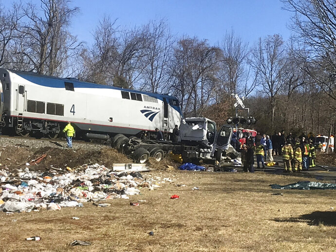 FILE - In this Wednesday, Jan. 31, 2018 file photo, emergency personnel work at the scene of a train crash involving a garbage truck struck by a train carrying Republican congressmen in Crozet, Va. Federal investigators have released nearly 100 documents that detail last year's fatal accident. National Transportation Safety Board spokesman Keith Holloway said the information was made public Tuesday, March 19, 2019