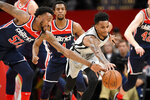 San Antonio Spurs guard Dejounte Murray, right, and Washington Wizards guard Jordan McRae (52) reach for the ball during the first half of an NBA basketball game Wednesday, Nov. 20, 2019, in Washington. (AP Photo/Nick Wass)