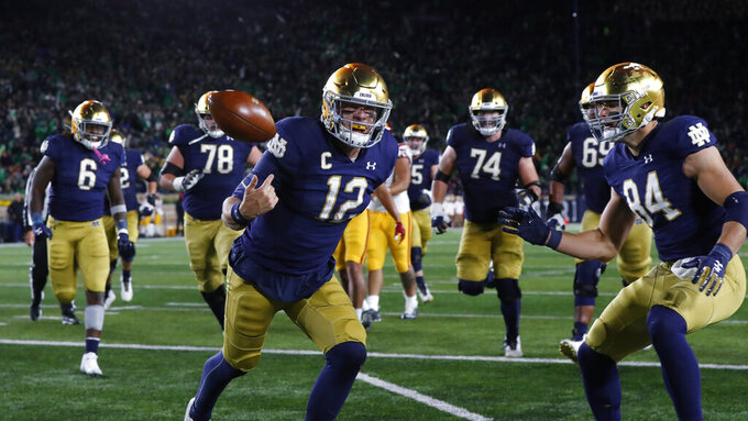 Notre Dame quarterback Ian Book (12) celebrates his 8-yard touchdown run in the second half of an NCAA college football game against Southern California in South Bend, Ind., Saturday, Oct. 12, 2019. (AP Photo/Paul Sancya)