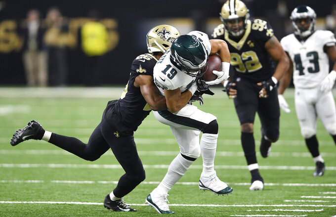 New Orleans Saints cornerback Eli Apple (25) tackles Philadelphia Eagles wide receiver Golden Tate (19) in the first half of an NFL divisional playoff football game in New Orleans, Sunday, Jan. 13, 2019. (AP Photo/Bill Feig)