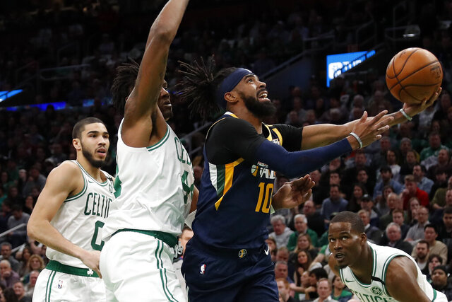 Utah Jazz's Mike Conley (10) goes to the basket past Boston Celtics' Robert Williams III during the first quarter of an NBA basketball game Friday, March 6, 2020, in Boston. (AP Photo/Winslow Townson)