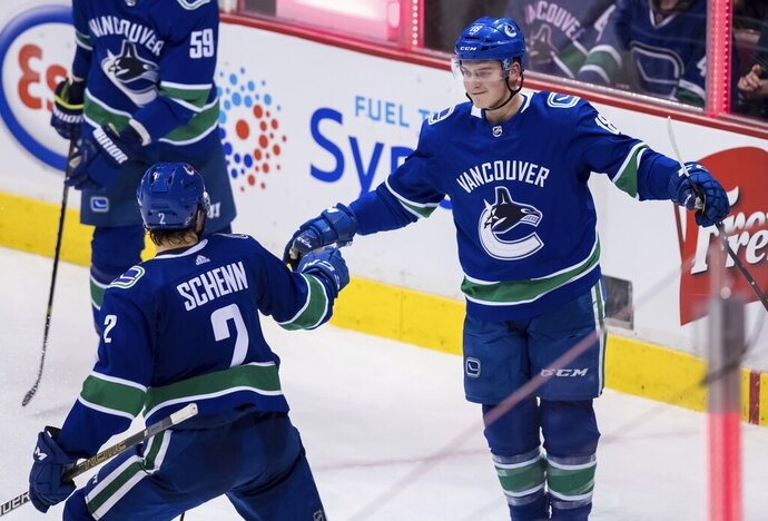 Vancouver Canucks' Jake Virtanen, right, and Luke Schenn celebrate Virtanen's goal against the Ottawa Senators during the second period of an NHL hockey game Wednesday, March 20, 2019, in Vancouver, British Columbia. (Darryl Dyck/The Canadian Press via AP)