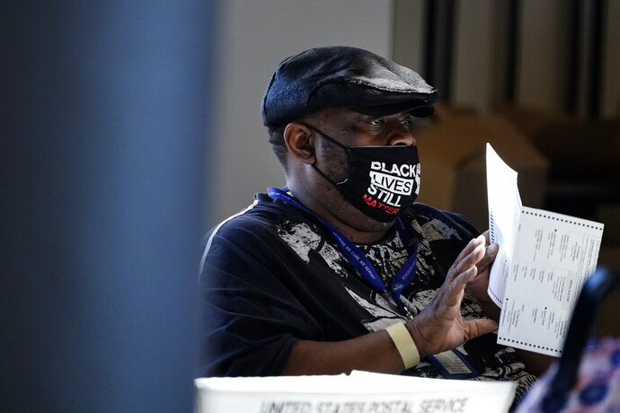 FILE - In this Nov. 4, 2020, file photo, an election worker holds a ballot as vote counting in the general election continues at State Farm Arena in Atlanta. President-elect Joe Biden won in Michigan, Wisconsin, Pennsylvania and Georgia because of Black voters, many of them concentrated in big cities. (AP Photo/Brynn Anderson, File)