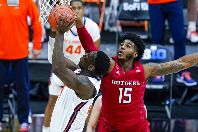 Illinois center Kofi Cockburn (21) is fouled by Rutgers center Myles Johnson (15) during the second half of an NCAA college basketball game at the Big Ten Conference men's tournament in Indianapolis, Friday, March 12, 2021. (AP Photo/Michael Conroy)