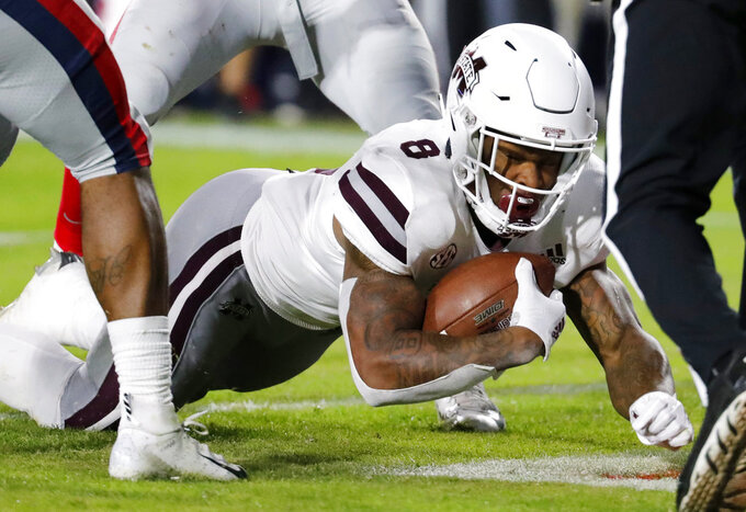 Mississippi State running back Kylin Hill (8) dives into the end zone for a 6-yard touchdown against Mississippi during the first half of an NCAA college football game in Oxford, Miss., Thursday, Nov. 22, 2018. (AP Photo/Rogelio V. Solis)
