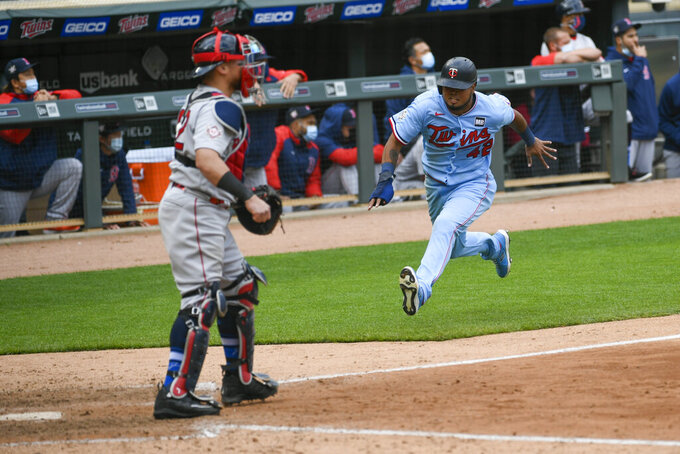 Minnesota Twins' Jorge Polanco, right, races home to scores the winning run on a single by Max Kepler as Boston Red Sox catcher Christian Vazquezwaits for the throw in the ninth inning of a baseball game, Thursday, April 15, 2021, in Minneapolis. The Twins won 4-3. (AP Photo/Craig Lassig)
