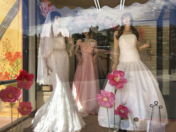 FILE - Mannequins in wedding gowns are seen in a window display on March 15, 2021, at a bridal store in Nogales, Ariz., that has been closed for nearly a year because of the pandemic. Couples in the U.S. are racing to the altar amid a vaccination-era wedding boom that has venues and other vendors in high demand. (AP Photo/Suman Naishadham, File)