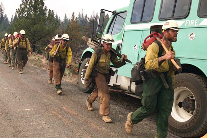 In this photo provided by the Bootleg Fire Incident Command, a handcrew walks to engage the Bootleg Fire in southern Oregon on Monday, July 19, 2021. The Oregon fire has ravaged the southern part of the state and has been expanding by up to 4 miles (6 kilometers) a day, pushed by gusting winds and critically dry weather that's turned trees and undergrowth into a tinderbox. (Bootleg Fire Incident Command via AP)