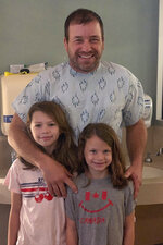"This undated photo provided by Roush Racing shows NASCAR driver Ryan Newman and his daughters, Brooklyn Sage, left, and Ashlyn Olivia, at Halifax Medical Center in Daytona Beach, Fla. Newman is fully alert, walking around the hospital and joking with staff two days after his frightening accident on the final lap of the Daytona 500 auto race. Roush Fenway Racing said Wednesday, Feb. 19, 2020, the 42-year-old ""continues to show great improvement."" (Roush Racing via AP)"