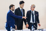 Swimmer Sun Yang, center, from China, arrives for a  public hearing at the Court of Arbitration for Sport (CAS) in Montreux, Switzerland, Friday, Nov. 15 2019. One of China's biggest Olympic stars and three-time gold medalist swimmer Sun Yang is facing a World Anti-Doping Agency appeal in Switzerland that seeks to ban him for up eight years for allegedly refusing to give samples voluntarily. (Jean-Christophe Bott/Keystone via AP)
