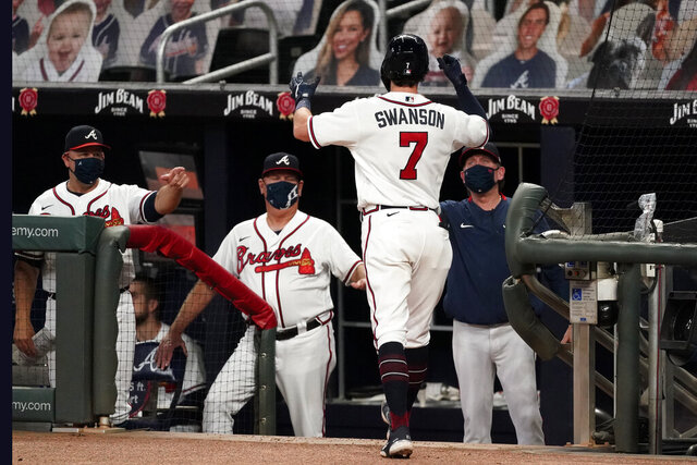 Atlanta Braves shortstop Dansby Swanson (7) is greeted by manager Brian Snitker and coach Walt Weiss, left, at the dugout after hitting a three-run home run in the fourth inning of a baseball game against the Miami Marlins Wednesday, Sept. 23, 2020, in Atlanta. (AP Photo/John Bazemore)