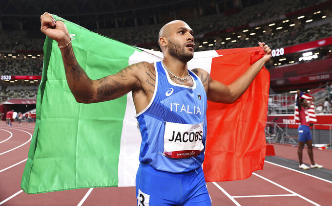 Lamont Marcell Jacobs of Italy celebrates after winning the final of the men's 100-meters at the 2020 Summer Olympics, Sunday, Aug. 1, 2021, in Tokyo, Japan. (Cameron Spencer/Pool Photo via AP)