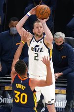 Utah Jazz forward Joe Ingles (2) shoots as Golden State Warriors guard Stephen Curry (30) defends during the second half of an NBA basketball game Saturday, Jan. 23, 2021, in Salt Lake City. (AP Photo/Rick Bowmer)