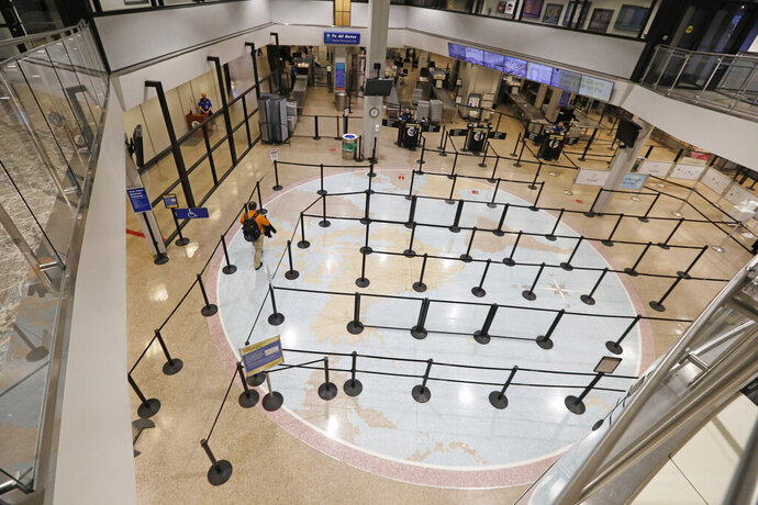 A traveler walks through the security line at the Salt Lake City International Airport Wednesday, March 25, 2020, in Salt Lake City. Many airline flights are nearly empty as virus undercuts travel. The Salt Lake City International Airport is expecting to screen about 5,000 passengers Wednesday, March 25, 2020, which is down from about 24,000 daily passengers. Earlier this year during the ski season, the airport was seeing record-breaking days with 30,000 passengers. (AP Photo/Rick Bowmer)