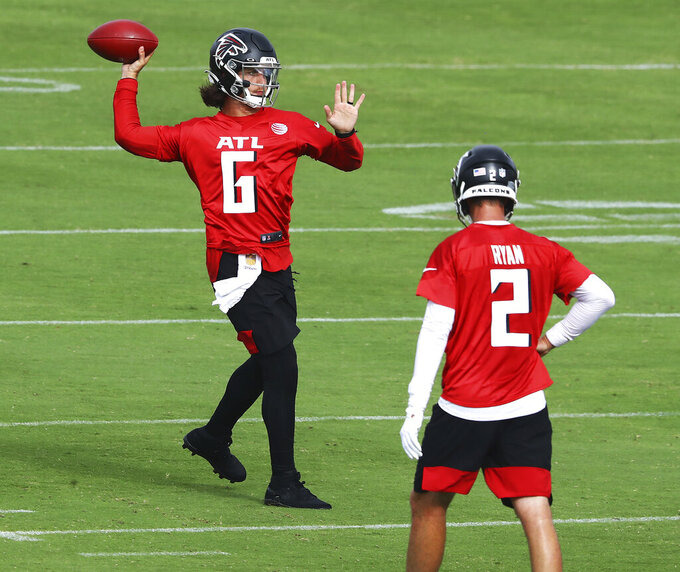 Atlanta Falcons backup quarterback Kurt Benkert completes a pass with Matt Ryan looking on during NFL football training camp practice Saturday, Aug. 15, 2020, in Flowery Branch, Ga.  (Curtis Compton/Atlanta Journal-Constitution via AP)