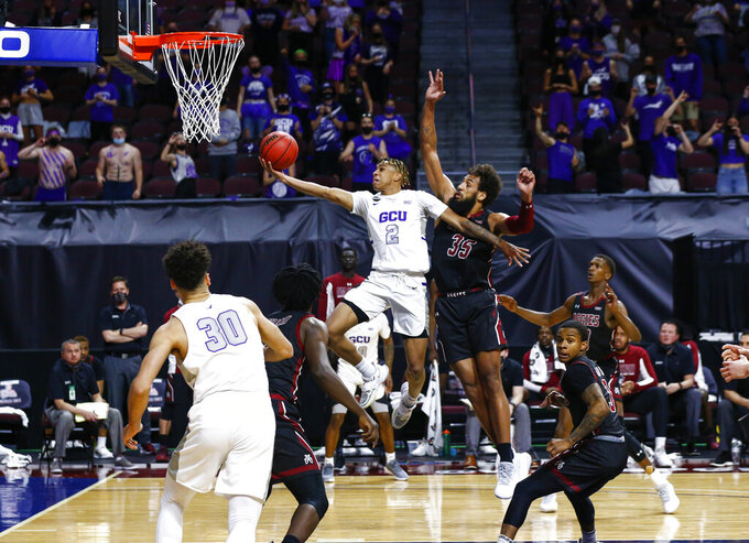 Grand Canyon's Chance McMillian (2) lays the ball up as New Mexico State's Johnny McCants (35) defends during the first half of an NCAA college basketball game for the championship of the Western Athletic Conference men's tournament Saturday, March 13, 2021, in Las Vegas. (AP Photo/Chase Stevens)