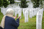 A woman prays at the memorial cemetery in Potocari, near Srebrenica, Bosnia, Tuesday, July 7, 2020. A quarter of a century after they were killed in Sreberenica, eight Bosnian men and boys will be laid to rest Saturday, July 11. Over 8,000 Bosnian Muslims perished in 10 days of slaughter after the town was overrun by Bosnian Serb forces in the closing months of the country's 1992-95 fratricidal war. (AP Photo/Kemal Softic)