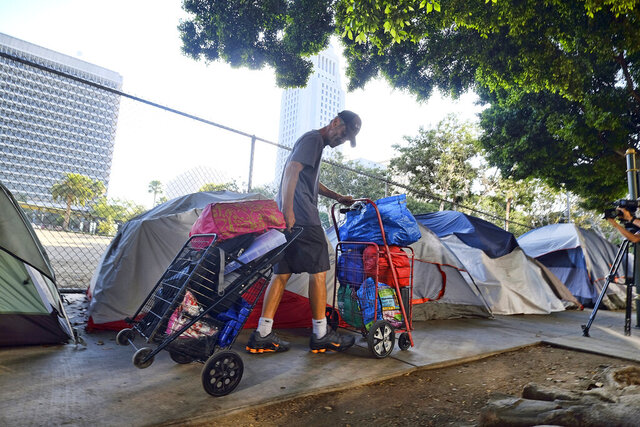 FILE - In this July 1, 2019, file photo, a homeless man moves his belongings from a street near Los Angeles City Hall, background, as crews prepared to clean the area. A report issued by the state's Legislative Analyst Office, Tuesday, Feb. 11, 2020, said Newsom's recently released 2020-2021 state budget