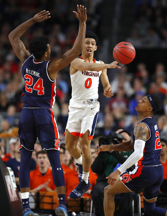 Virginia guard Kihei Clark (0) passes between Auburn's Anfernee McLemore, left, and Bryce Brown, right, during the second half in the semifinals of the Final Four NCAA college basketball tournament, Saturday, April 6, 2019, in Minneapolis. (AP Photo/Charlie Neibergall)