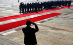 A protocol staff member takes photo of members of the Serbian Honor guard prepare for a welcome ceremony for visiting of Russian Defense Minister Sergei Shoigu in Belgrade, Serbia, Monday, Feb. 17, 2020. Shoigu is on a one-day official visit to Serbia. (AP Photo/Darko Vojinovic)