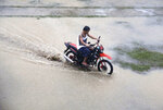 A resident rides his motorcycle across a flooded area as rains from Typhoon Mangkhut begin to affect Tuguegarao city, Cagayan province, northeastern Philippines on Friday, Sept. 14, 2018. Typhoon Mangkhut retained its ferocious strength and slightly shifted toward more densely populated coastal provinces on Friday as it barreled closer to the northeastern Philippines, where a massive evacuation was underway. (AP Photo/Aaron Favila)