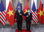 U.S. Secretary of State Mike Pompeo, left, and Vietnamese Foreign Minister Pham Binh Minh gesture with their elbows while posing for a photo before a meeting in Hanoi, Vietnam, Friday, Oct. 30, 2020. Pompeo is wrapping up an anti-China tour of Asia in Vietnam as the fierce American presidential election race enters its final stretch. (Bui Lam Khanh/VNA via AP)